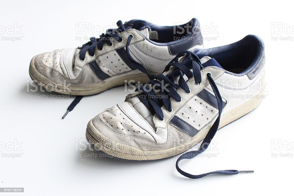 Pair of worn, white vintage sneakers stock photo