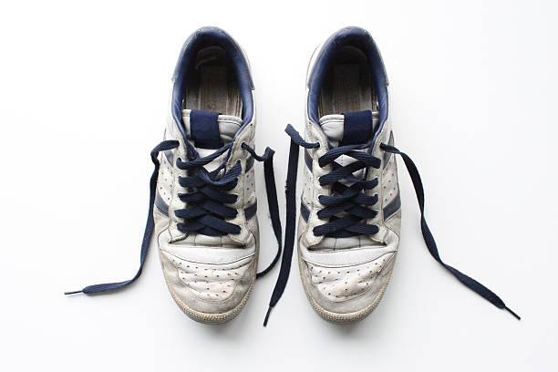 pair of worn, white vintage sneakers shot from above - typisch 90er stock-fotos und bilder