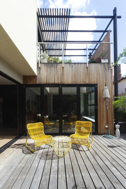 Pair of yellow cane outdoor chairs on wooden deck in contemporary courtyard Pair of yellow cane outdoor chairs on wooden deck in contemporary courtyard courtyard stock pictures, royalty-free photos & images