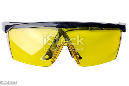 Pair of yellow safety goggles cut out on white a background. Tools series.