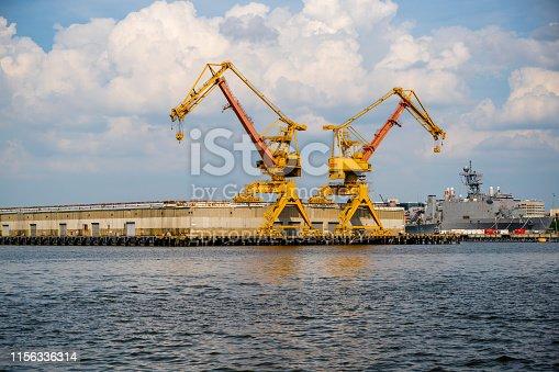 Norfolk, VA, USA -- June 6, 2019. Matching pair of yellow shipyard cranes  set against a bright blue sky in Port Virginia, Norfolk.