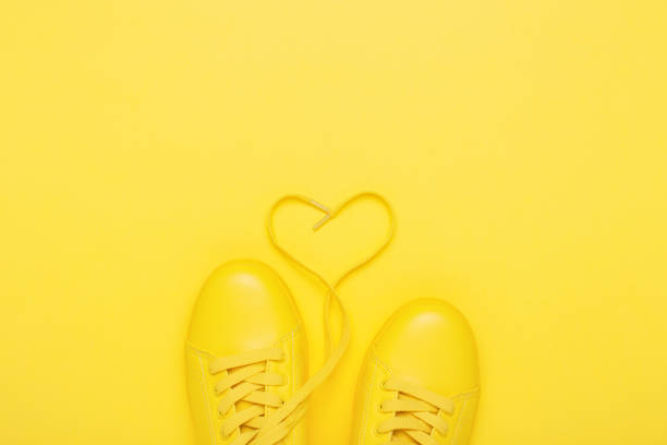 Pair of yellow shoes on yellow background. - foto stock