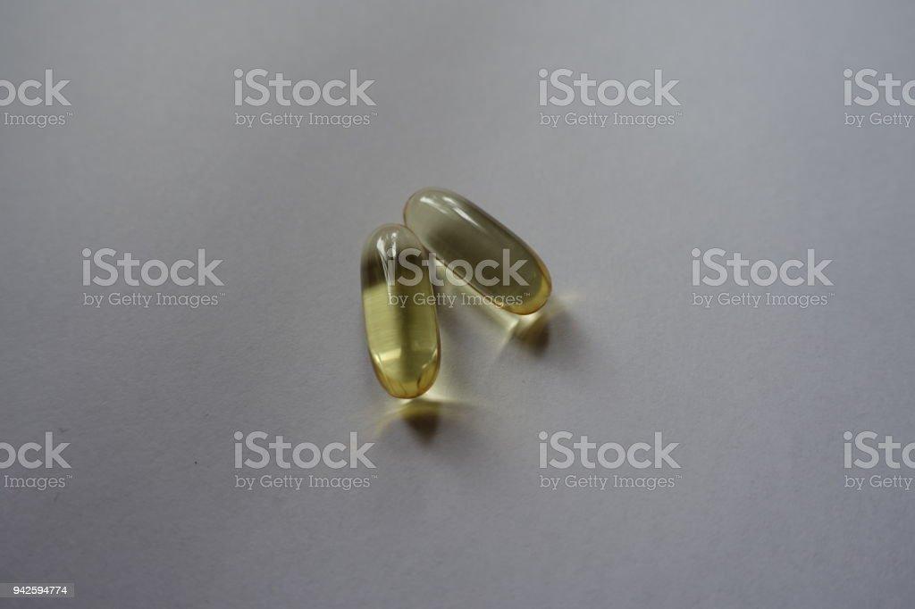 Pair of yellow softgel capsules of fish oil stock photo