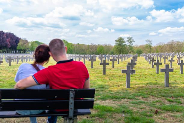 Ein Jugendpaar sitzt auf einer Bank mit Blick auf Betonkreuze auf dem deutschen Kriegsfriedhof in den Niederlanden. – Foto
