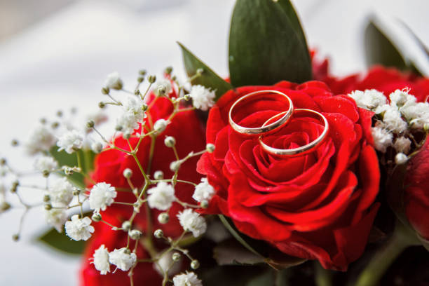 Pair or wedding rings on bouquet flower stock photo