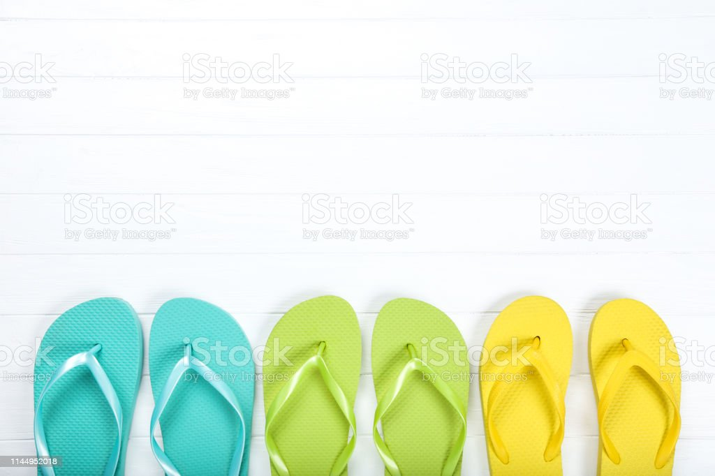 Pairs of colorful flip flops on white wooden table