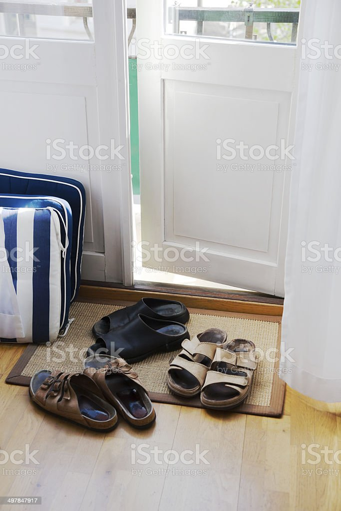 Pairs Of Shoes By The Door To The Balcony. Stock Photo