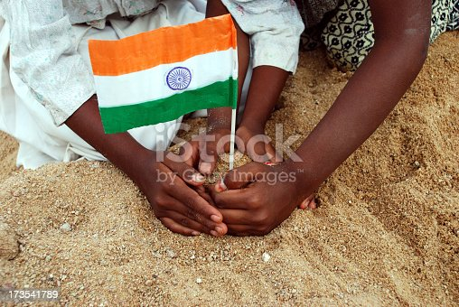 istock Pairs of young hands plant a miniature Indian flag in sand 173541789
