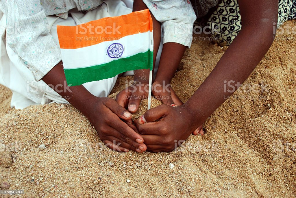 Pairs of young hands plant a miniature Indian flag in sand stock photo