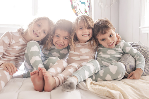 4 young children smile and goof around for a group picture in their pajamas