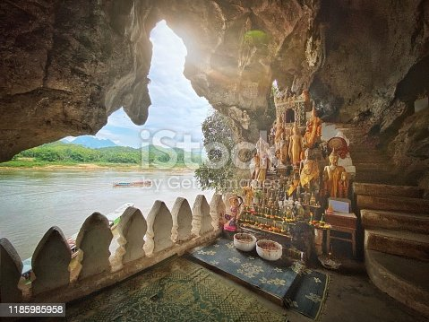 Sunbeam into the Pak Ou Cave Buddha Shrine at Tham Ting Buddhist Cave. Pak Ou, Mekong River, Luang Prabang, Laos, Southeast Asia.