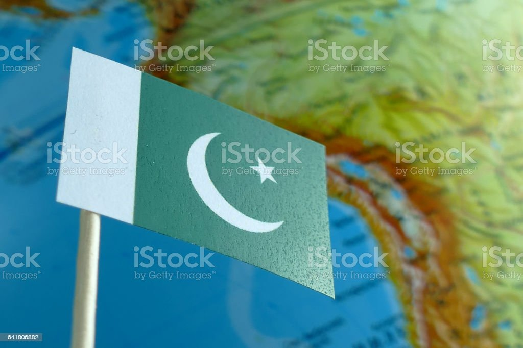 Pakistan flag with a globe map as a background macro stock photo