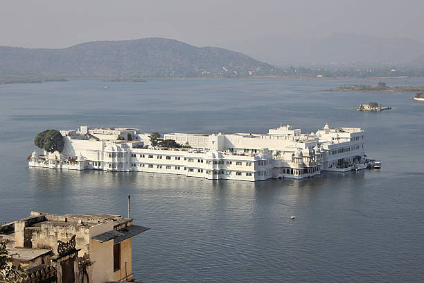 Palace amidst Lake Pichola View of picturesque Pichola Lake surrounded by mountains housing Lake Palace, Udaipur, Rajasthan, India, Asia lake palace stock pictures, royalty-free photos & images