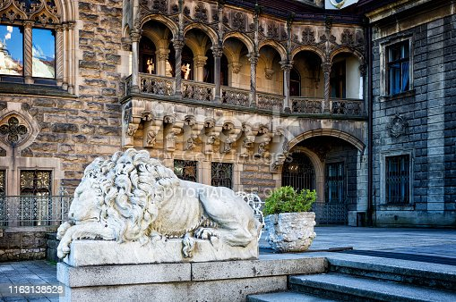 Moszna, Poland - September 01, 2016:Lion sculpture on the background of the Palace facade in neo-gothic style in Moszna, Poland. Palace was built at the turn of the nineteenth and twentieth centuries.