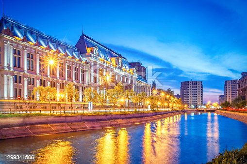 The Palace of Justice on the banks of the Dambovita River in Bucharest, Romania at twilight blue hour. It was built between 1890-1895 and it houses the Bucharest Court of Appeal.