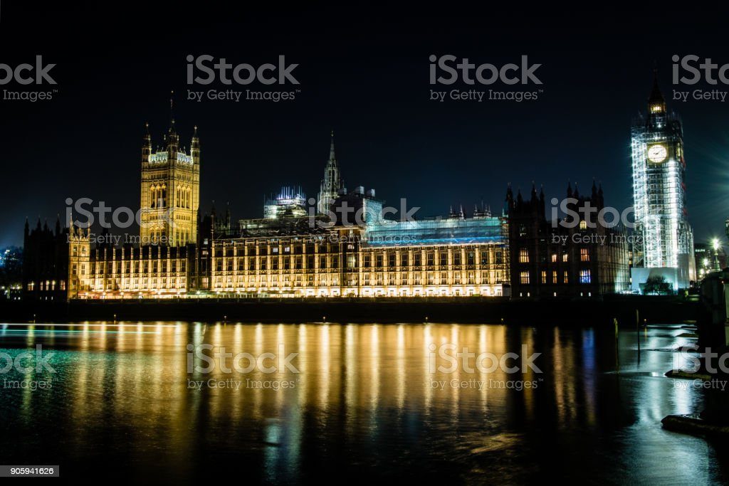 Palaces of Westminster lit up at night with Big Ben still under construction stock photo