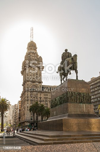 Montevideo, Uruguay- December 18, 2008: Statue of Jose Gervasio Artigas on his horse on top of stone pedestal looking at Palacio Salvo under silver sky. Palm trees and people.