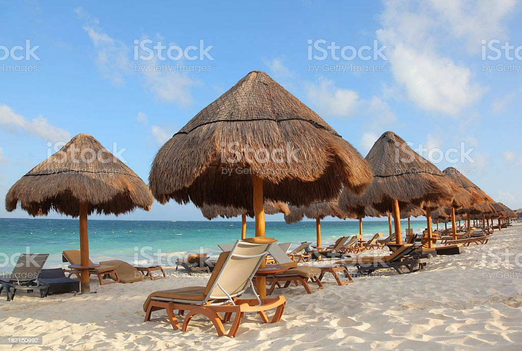 Palapas and Chairs on a tropical beach stock photo