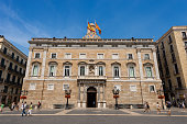 Barcelona, Spain, June 13, 2014: Palau de la Generalitat de Catalunya (XV-XVII century) in Barcelona, Spain - neoclassical facade. It houses the offices of the Presidency of the Generalitat de Catalunya. It is one of the few buildings of medieval origin in Europe that still functions as a seat of government and houses the institution that originally built it. Tourists and locals stroll through the town square (Placa de Sant Jaume).