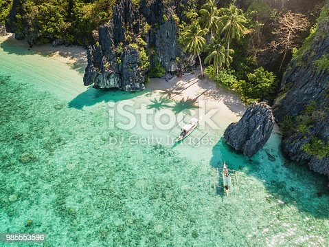 Beautiful Entalula Island Beach Lagoon with typical filipino Balangay Boats. Aerial Drone Point of View. Bacuit Bay, Mimaropa, El Nido, Palawan, Philippines, Asia