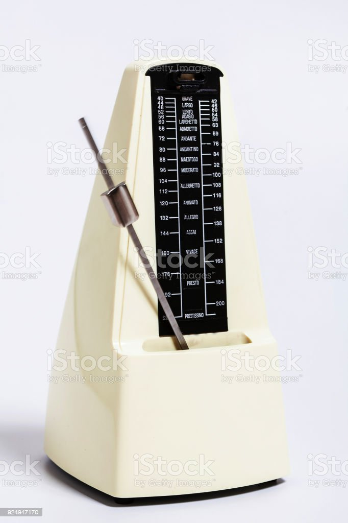 Pale beige metronome in motion on white background. keep a beat. stock photo