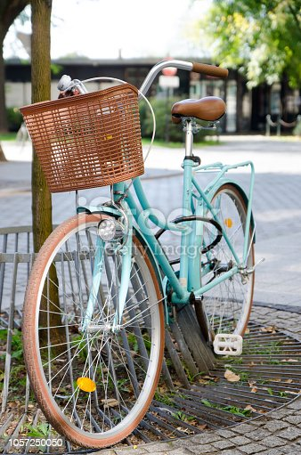 Pale blue bicycle standing on a pole during summer day