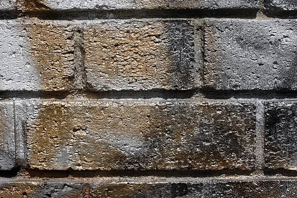 sprayed graffiti wall bricks in orange gold and grey - whiteway graffiti stock photos and pictures