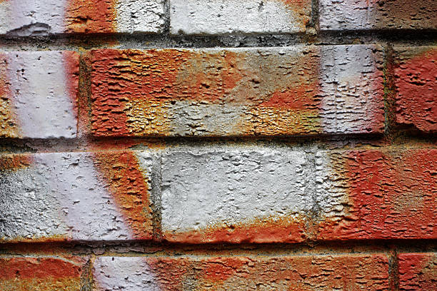 spray paint graffiti wall bricks in bright orange and white - whiteway graffiti stock photos and pictures