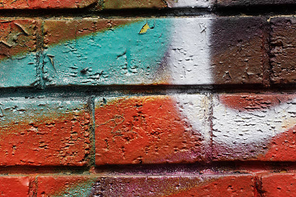 spray paint design wall bricks in bold colours - whiteway graffiti stock photos and pictures