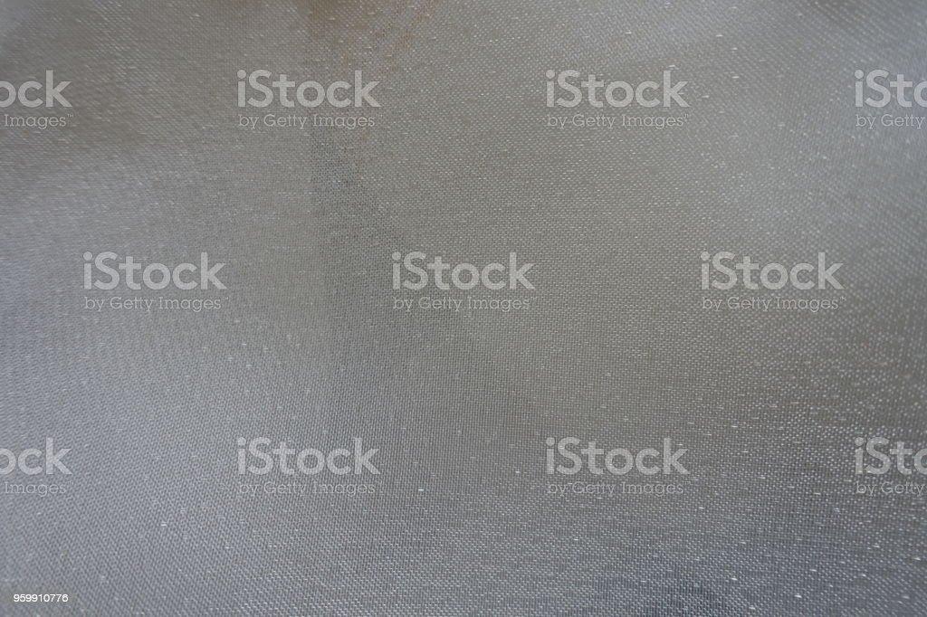 Pale cream colored thin shiny sheer fabric stock photo