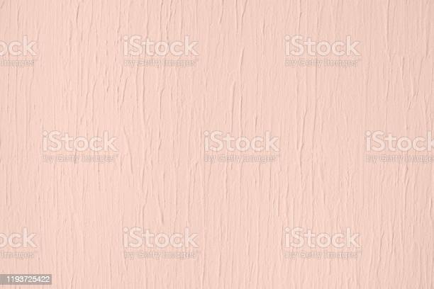 Photo of Pale pink colored low contrast Concrete textured background with roughness and irregularities