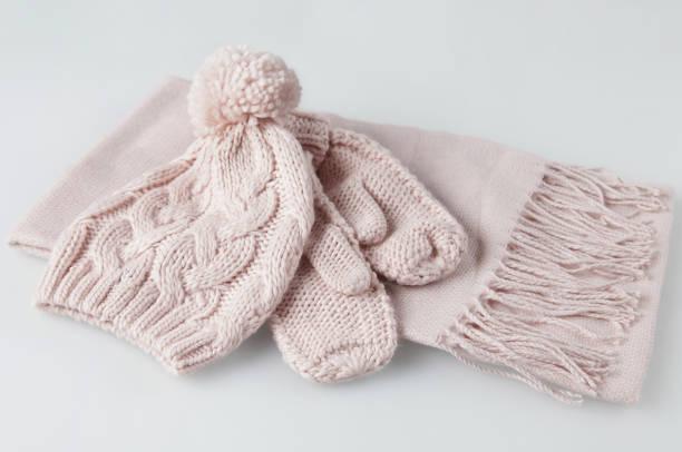 blass rosa handschuhe, schal und wollmütze frau winter setzen auf weißem hintergrund - mützenschal stock-fotos und bilder