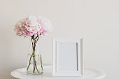 Close up of pale pink peonies in glass vase with blank rectangular picture frame on white table - matte filter effect and selective focus