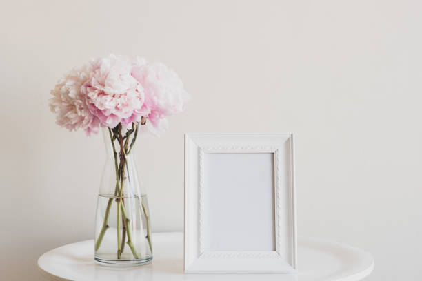 Pale pink peonies with blank rectangular picture frame on table stock photo