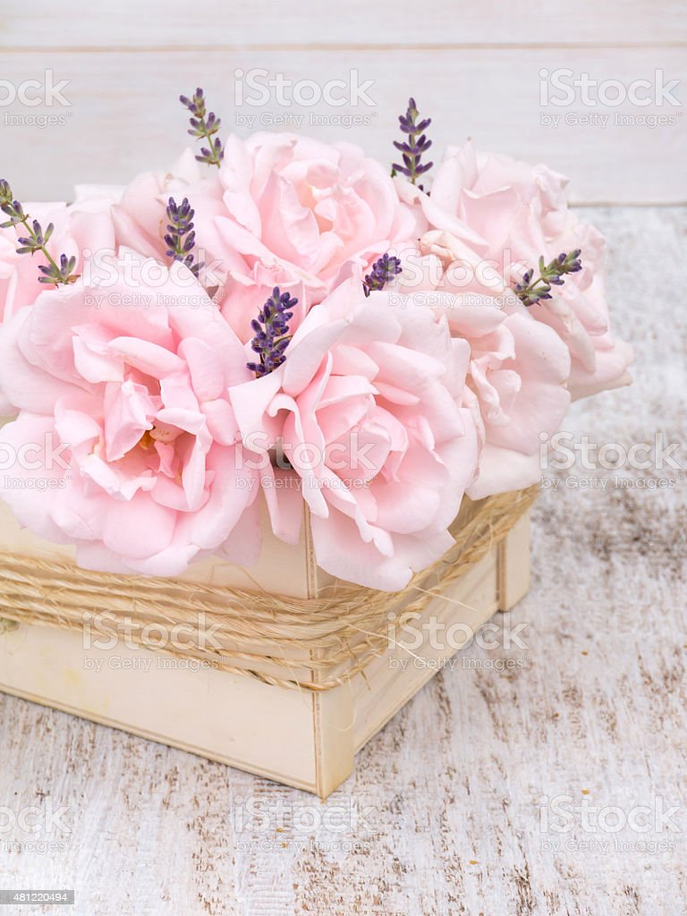 Pale pink roses and lavender bouquet in the wooden box stock photo