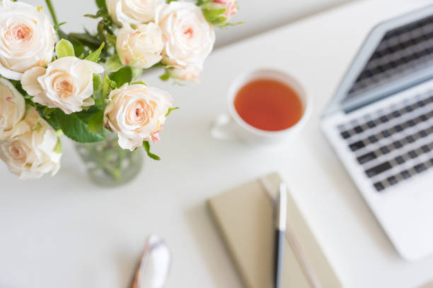 Pale pink roses on home office desk from above stock photo