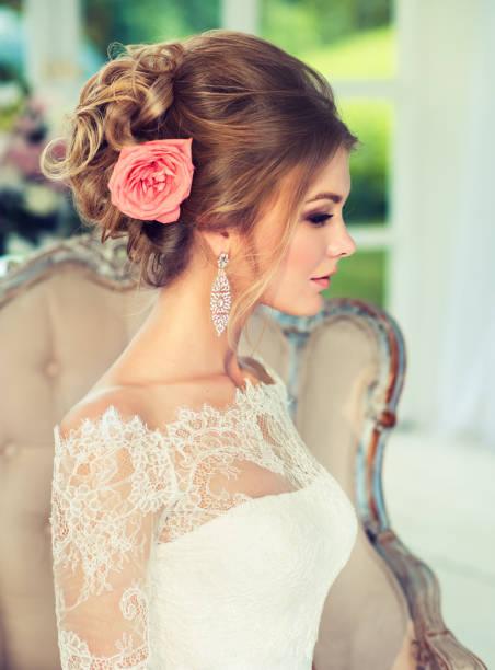 blasse rose rosa auf das voluminöse brautkleid haar. porträt im profil. - brautstyling stock-fotos und bilder