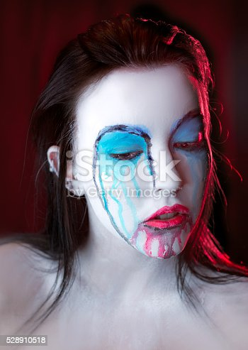 181894581 istock photo Pale Woman with dripping makeup and paint on her face 528910518
