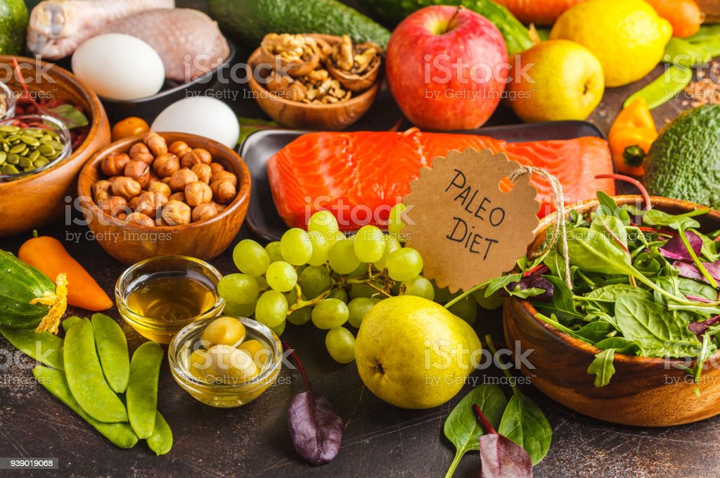 Paleo diet concept. Balanced food background on the table. Copy space, dark background. Fresh raw vegetables, fruits, meat, fish, top view. stock photo
