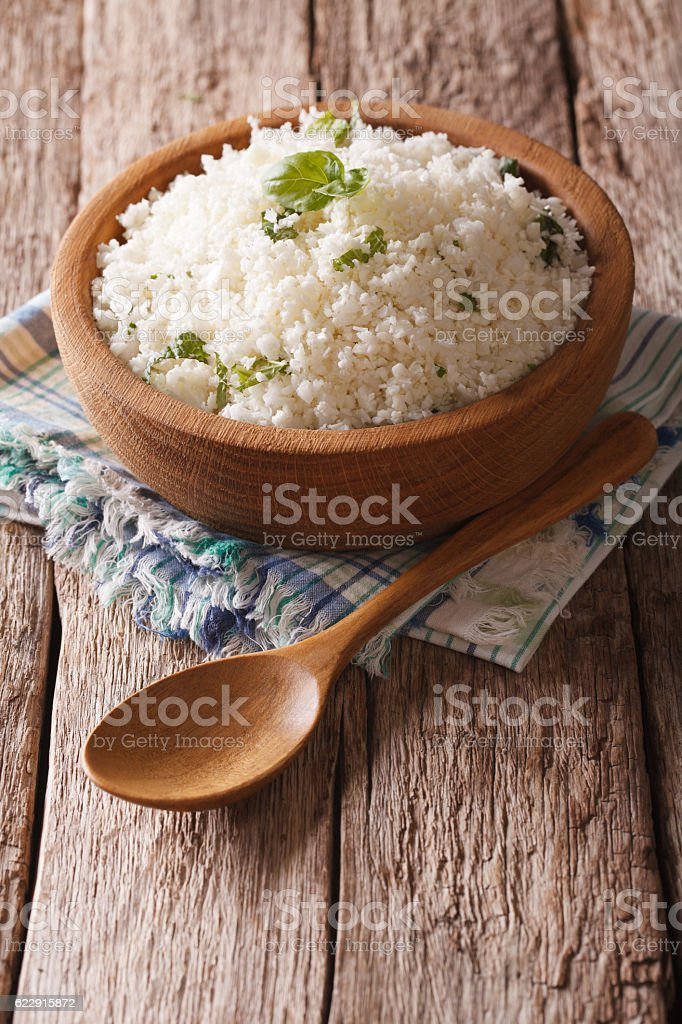 Paleo Food: Cauliflower rice with herbs close-up. Vertical stock photo
