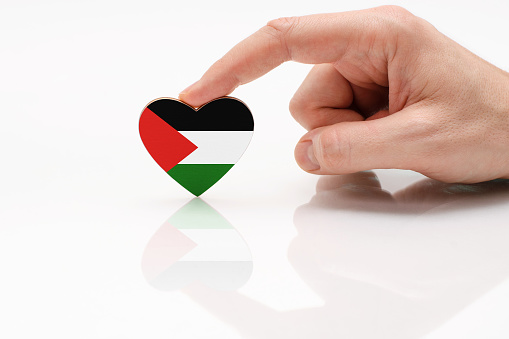 Palestine flag. Love and respect Palestine. A man's hand holds a heart in the shape of the Palestine flag on a white glass surface. The concept of patriotism and pride.