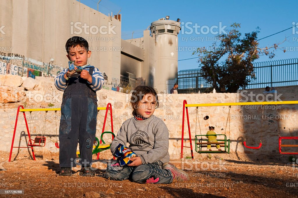 Palestinian children at playground beside Separation Barrier wall in Bethlehem stock photo