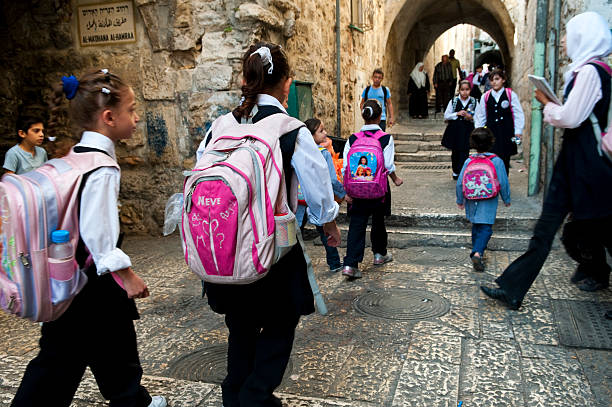 Palestinian children walking to school in East Jerusalem Palestinian children walk to school in the Muslim Quarter of Jerusalem's Old City. muslim quarter stock pictures, royalty-free photos & images