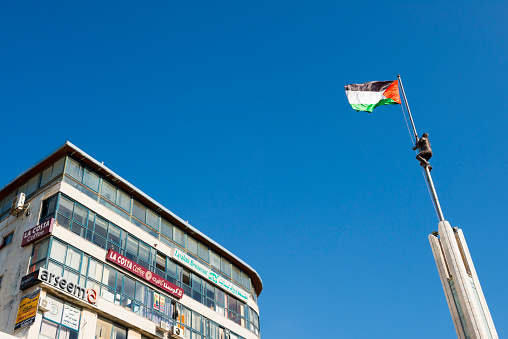 Ramallah, West Bank, Palestinian Territories - July 22, 2013: A clear blue sky is seen above the West Bank city of Ramallah. To the left is a building housing several businesses; to the right is a monument featuring the Palestinian flag.
