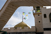 Palestinian flags fly above a mosque in the West Bank village of Bil'in