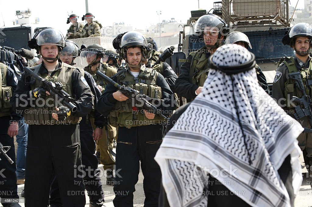 Palestinian man confronts Israeli soldiers stock photo