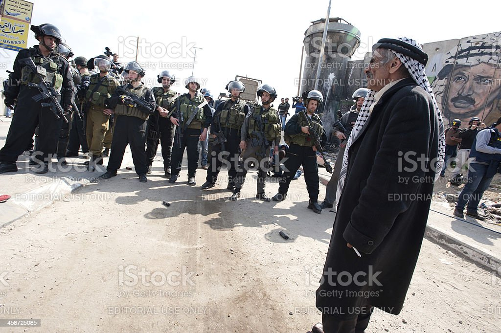 Palestinian man confronts Israeli soldiers royalty-free stock photo