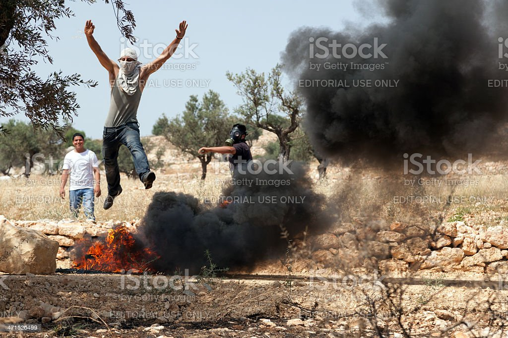 Palestinian Man Jumping over Fire at Protest stock photo