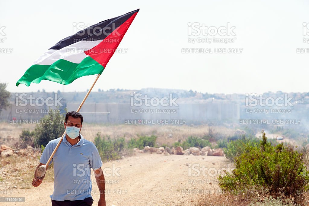 Palestinian Protester Holding Flag by Wall of Separation West Bank stock photo