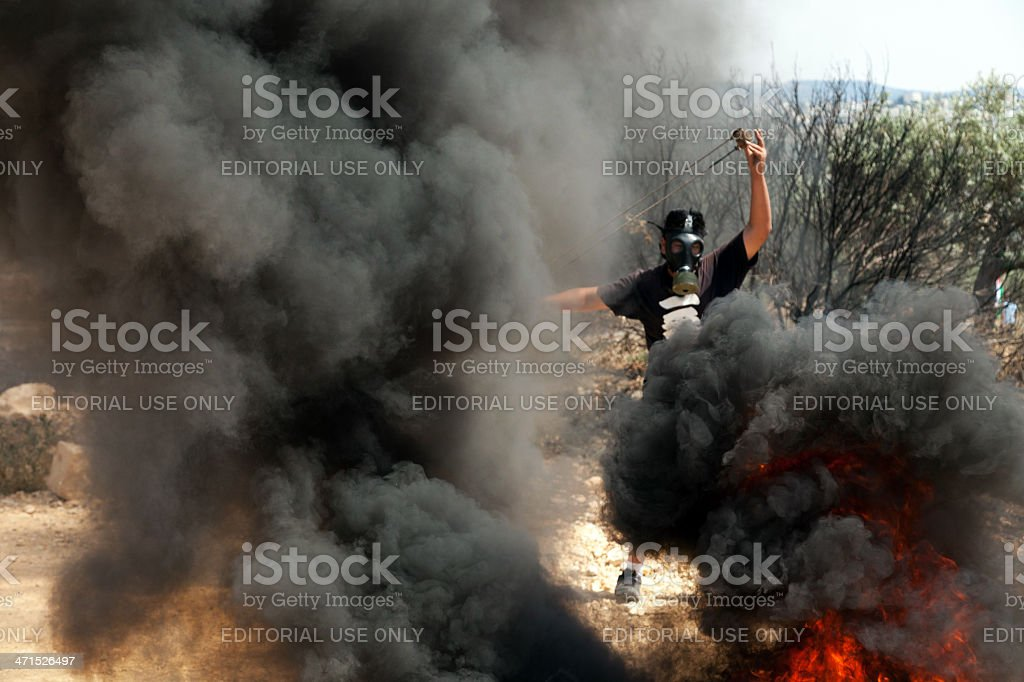 Palestinian Protester with Slingshot Amidst Smoke stock photo